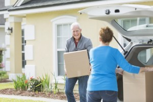 Senior couple moving boxes in trunk of car