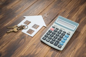 house and key with Calculator on wooden background