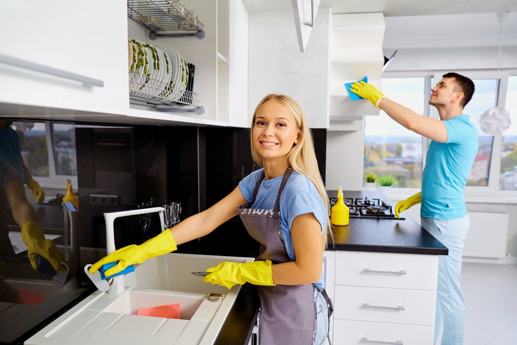 The couple is cleaning in the kitchen