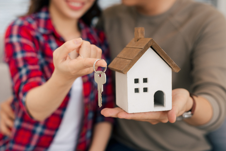 Proud young asian couple with keys and wooden house modelling