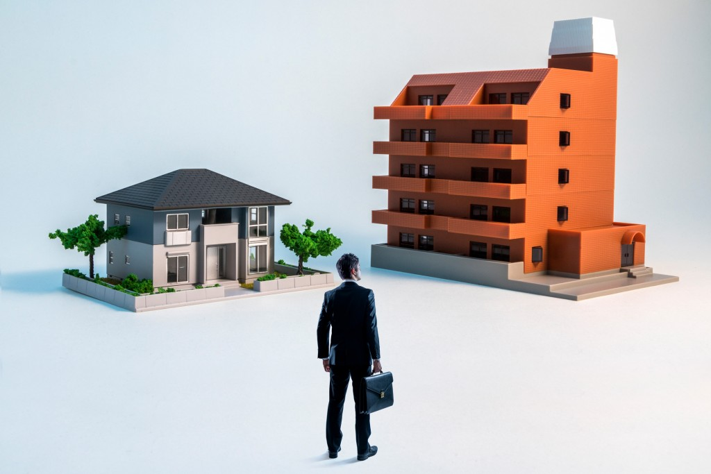 businessman looking at a house and a apartment building.