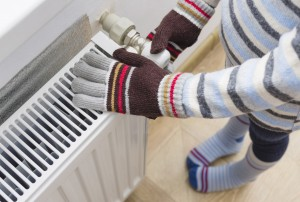 A child in woolen gloves and a sweater warms his hands near the heater.